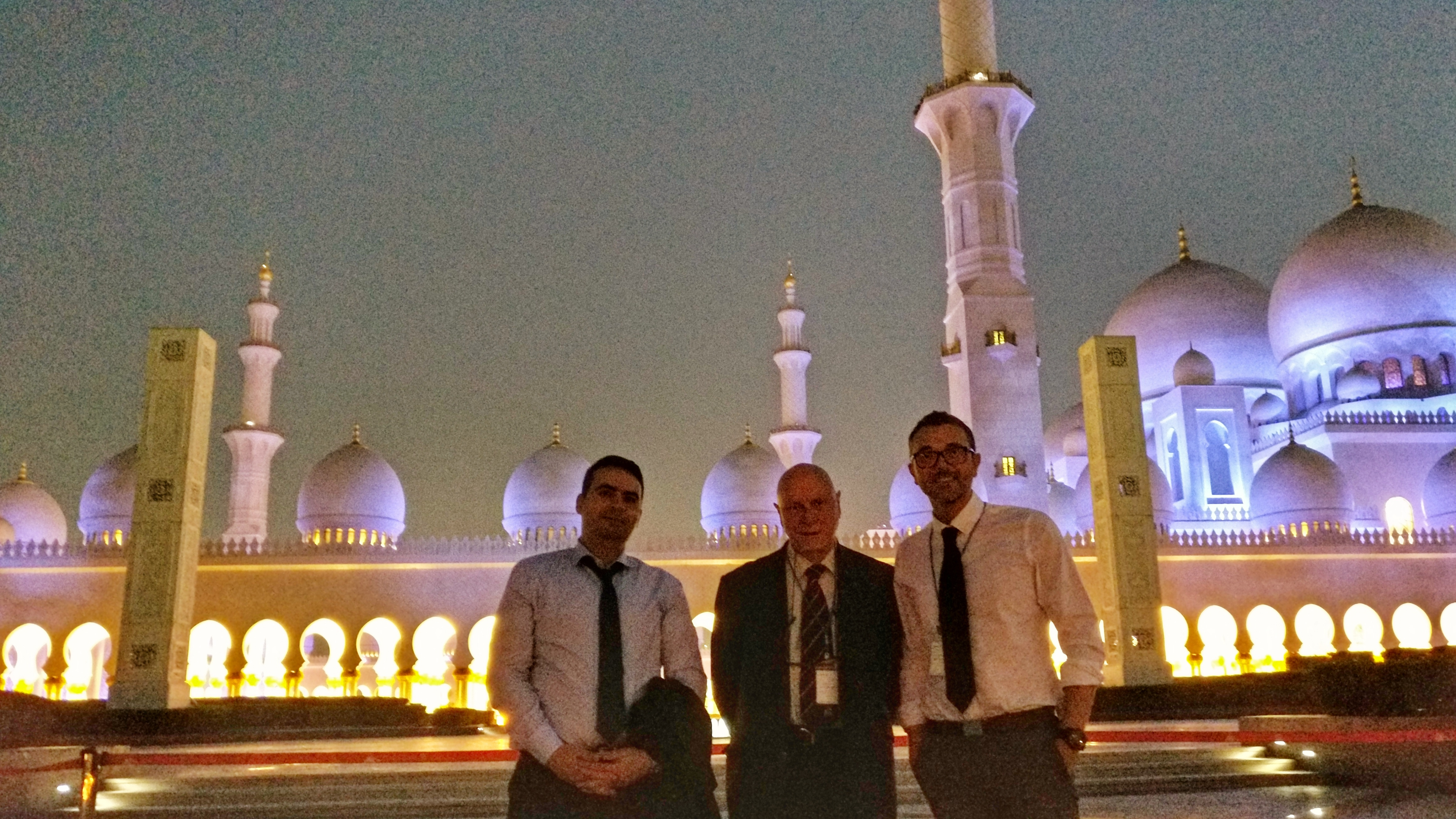 three men smiling in front of the Sheikh Zayed Grand Mosque