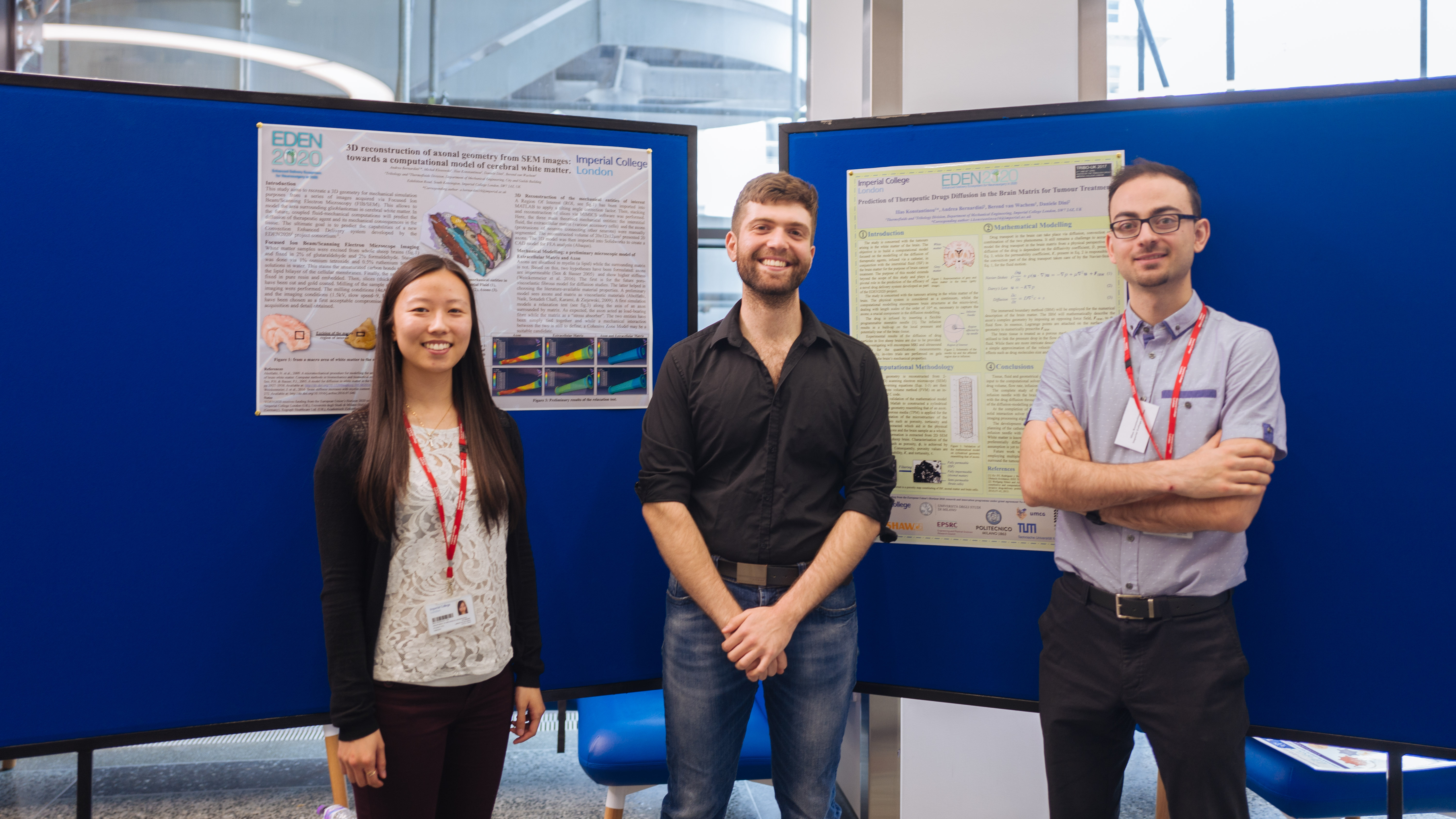 three people standing in front of EDEN science posters