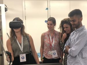 Marlene wearing virtual headset and 3 people looking on