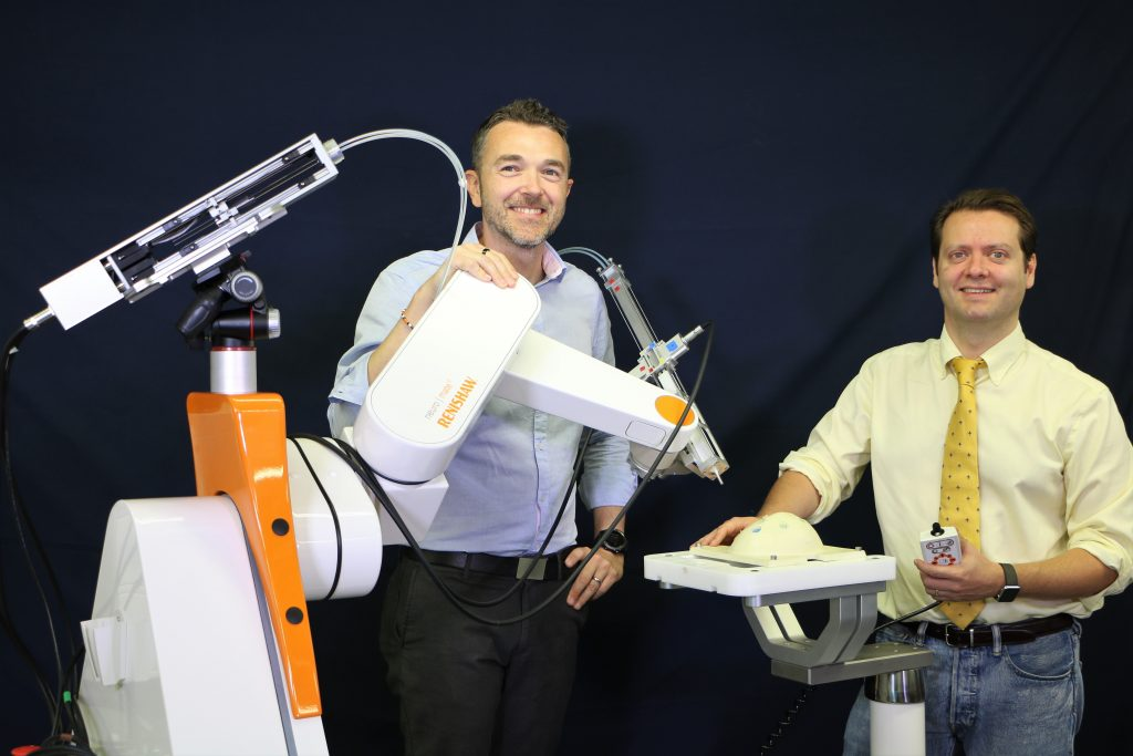 Riccardo and Ferdinando standing with the Eden robotic system