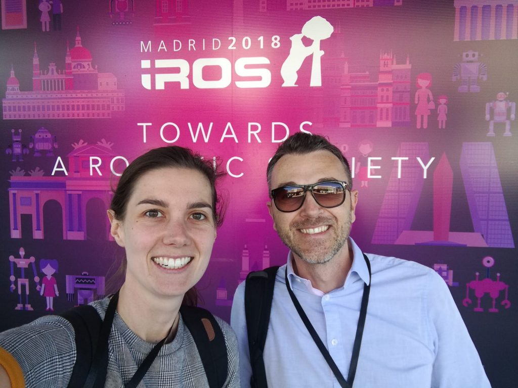 Eloise and Riccardo smiling in front of IROS2018 logo