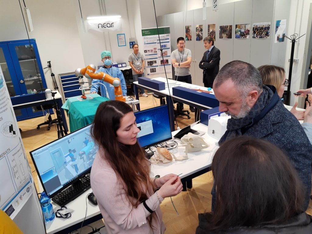 Alice speaking with a man and showing the EDEN steerable catheter at Leonardo Robotics Labs in Milan