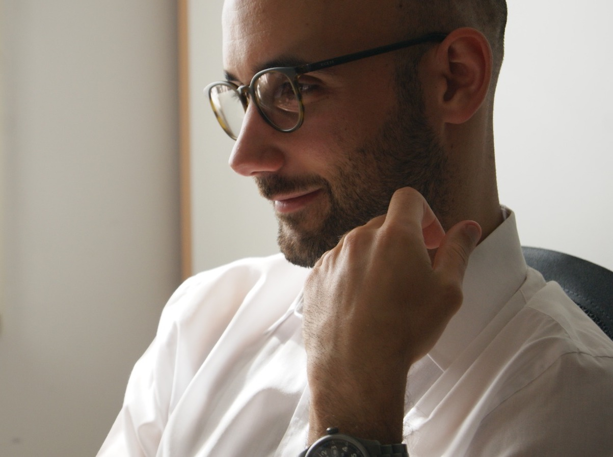 close-up photo of a man wearing spectacles looking to the left of camera