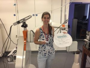 Eloise in front of the robotic delivery system holding EDEN2020's sterilised surgical package.